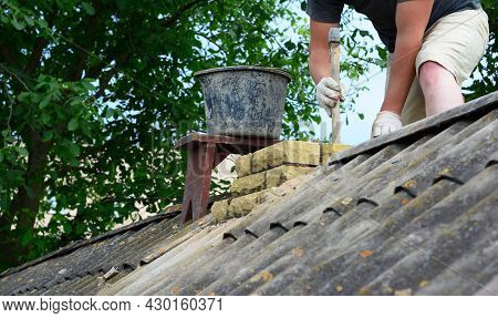 Masonry Chimney Construction. A Contractor Is Building, Repairing A Brick Chimney On The Ridge Of As