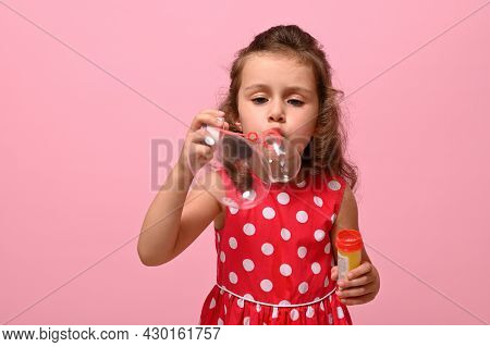 Cheerful Birthday Girl In Pink Polka Dots Dress Blowing Soap Bubbles, Isolated Over Pink Background