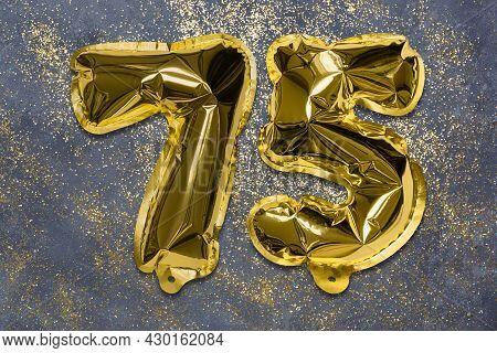 The Number Of The Balloon Made Of Golden Foil, The Number Seventy-five On A Gray Background With Seq