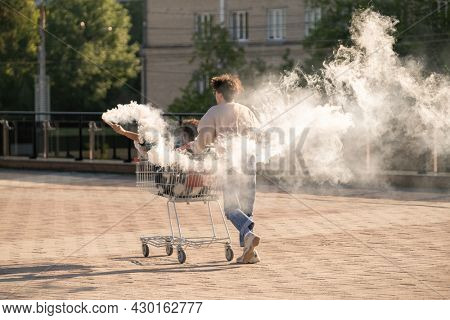 Ecstatic teenage dates having fun with firecrackers while guy pushing shopping cart with his girlfriend