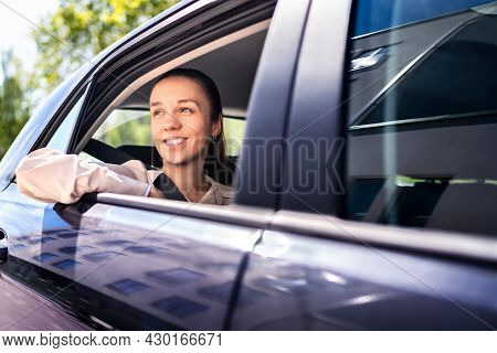 Woman In Car As Passenger On The Backseat. Smiling Female Customer In Taxi Cab Looking Out The Windo