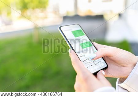 Texting Sms With Phone In City Outdoor Park. Woman Sending Text Message With Cellphone. Chatting On