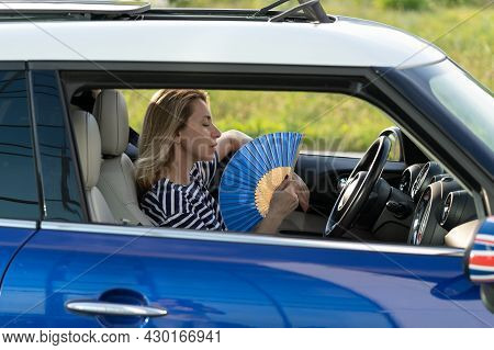 Exhausted Young Woman Driver With Hand Fan Suffering From Heat In Car, Has Problem With A Non-workin