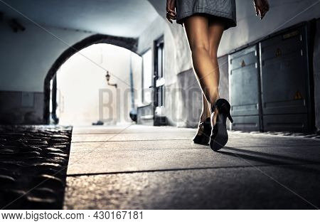 Woman In Dark Alley And City Street At Night Alone. Lonely Scared Girl Walking, Afraid Of Sexual Har