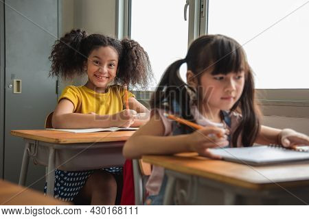 Portrait Of Asian Elementary School Kids Studying In A Class. The Girl Positive, Happy, Smiles And L