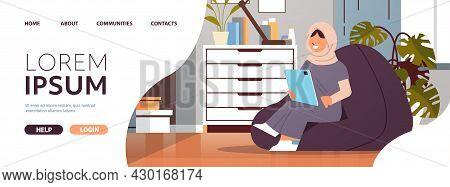 Arab Schoolgirl Using Tablet Pc Arabic Girl Sitting On Beanbag And Doing Homework Education Concept