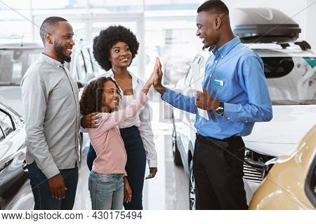 Lovely Black Girl High Fiving Friendly Salesman At Auto Dealership
