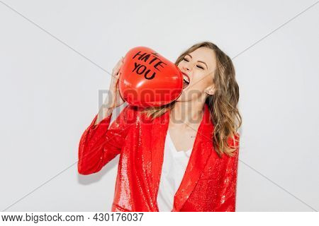 Woman in red jacket biting a red balloon with I Hate You text