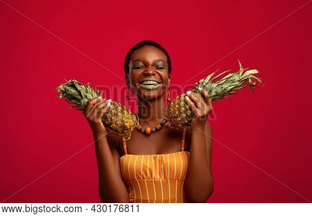 Ecstatic Afro American Woman Holding Pinapples And Laughing