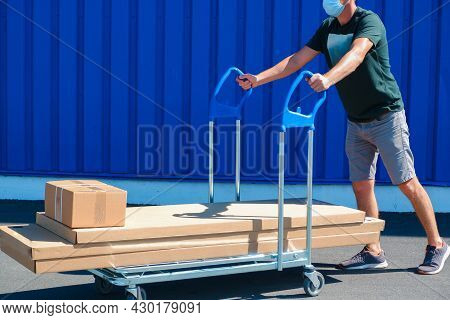 A Young Man In Shorts And A T-shirt Pulls A Cart With Cardboard Boxes. Man Pulling A Hand Truck Load