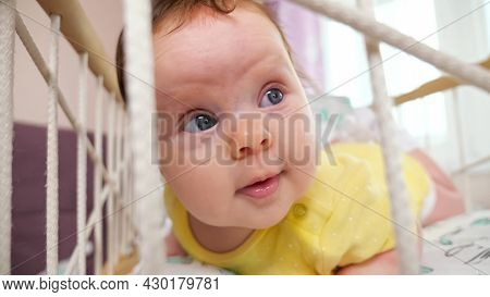 Joyful Baby Girl In Yellow Bodysuit Lies On Belly In Rocking Cradle Playing And Looking With Interes