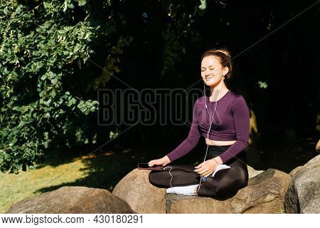 Meditation, Mindfulness, Yoga. Smiling Young Woman In Sportswear Listens Music On Headphones Using S