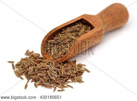 Cumin In Wooden Scoop Over White Background