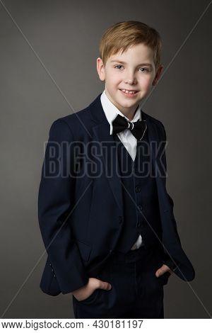 Elegant Little Boy In Classic Black Suit With Bowtie Over Gray. Smiling Child Gentleman In Smart Cas