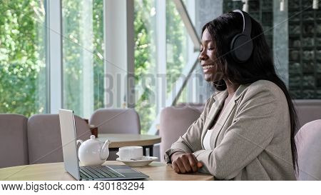 Cheerful Black Woman In Jacket With Headphones Talks On Videocall Via Contemporary Laptop Sitting At