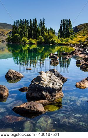 Cypress alley and huge basalt boulders reflected in the lake. The surroundings of the Cromwell. Magic New Zealand. The concept of ecological, landscape and photo tourism