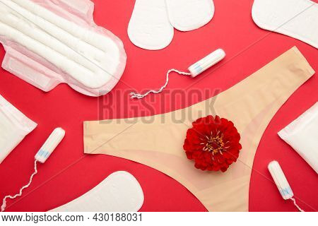 Women's Panties With Menstrual Pads And Tampons On Red Background. Top View. Concept Of Critical Day