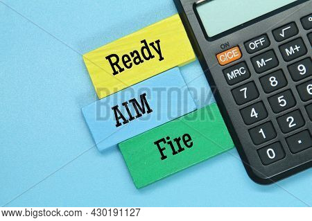 Calculator, Colored Board With Three Motivational Words Ready, Aim And Fire