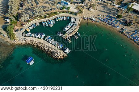 Aerial Drone View Of Agia Triada Beach With People Swimming And Fishing Boats Moored At The Harbor.