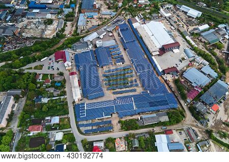 Aerial View Of Solar Power Plant With Blue Photovoltaic Panels Mounted On Industrial Building Roof F