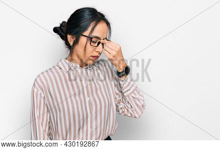 Young hispanic girl wearing casual clothes and glasses tired rubbing nose and eyes feeling fatigue and headache. stress and frustration concept.