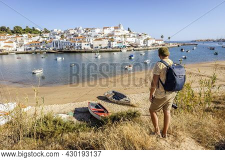 Cityscape Of Ferragudo With A Tourist Admiring This Town In The Foreground, Algarve, Portugal
