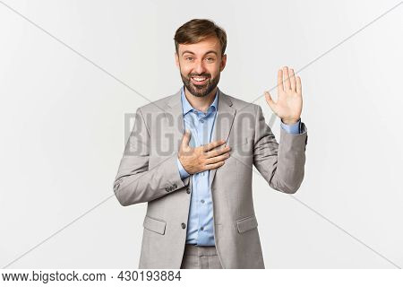 Portrait Of Smiling Bearded Businessman Making Promise, Raising Hand Up And Put Palm On Heart, Swear