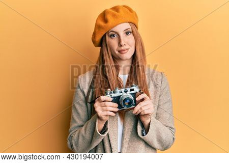 Young irish woman holding vintage camera relaxed with serious expression on face. simple and natural looking at the camera.