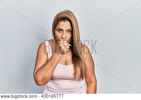 Middle age hispanic woman wearing casual style with sleeveless shirt feeling unwell and coughing as symptom for cold or bronchitis. health care concept.