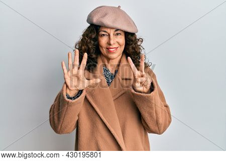 Middle age hispanic woman wearing french look with beret showing and pointing up with fingers number seven while smiling confident and happy.