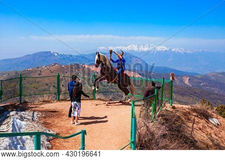 Chimgan, Uzbekistan - April 12, 2021: Tourist On Horse At The Chimgan Mountain Viewpoint And Tian Sh