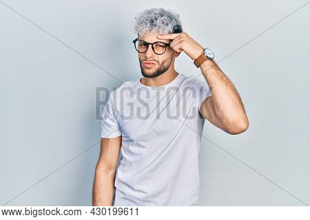Young hispanic man with modern dyed hair wearing white t shirt and glasses pointing unhappy to pimple on forehead, ugly infection of blackhead. acne and skin problem