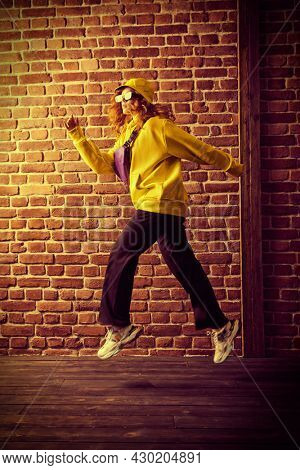 Cool street dancer girl in bright trendy clothes and sunglasses dancing and jumping by a brick wall background. Hip-hop dancer.