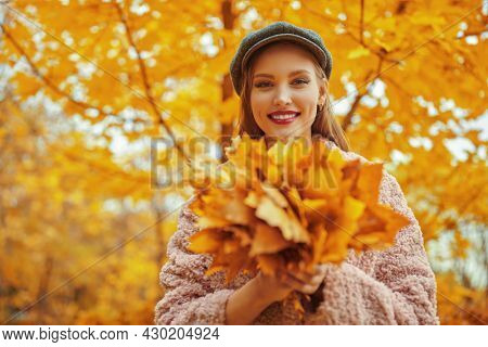 Happy autumn mood. Beautiful young woman walks in the autumn park with a bouquet of yellow maple leaves.