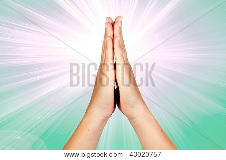 Hands clasped in prayer with rays of light on green background