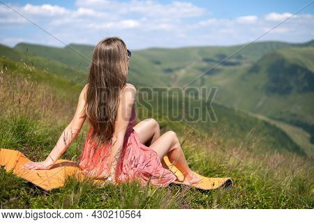 Young Woman In Red Dress Resting On Green Grassy Field On A Warm Sunny Day In Summer Mountains Enjoy