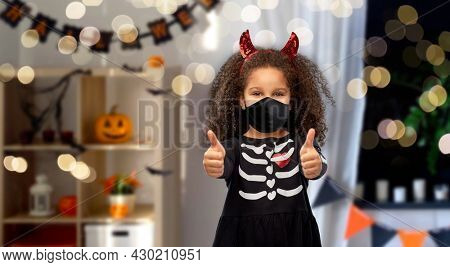 halloween, holiday and pandemic concept - african american girl in black protective mask and costume dress and red devil's horns over lights and decorated home room background