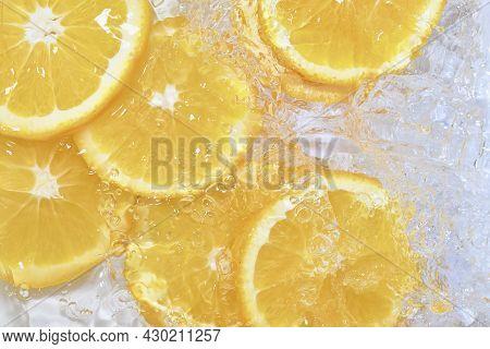 Oranges Close-up In Liquid With Bubbles. Slices Of Juicy Oranges In Water. Close-up Fresh Slices Of