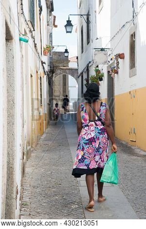 Coloured Woman Seen From Her Back Walking On An Old Street At Evora, Portugal. Wearing A Colorful Dr