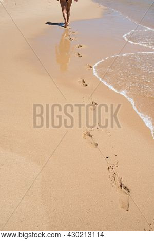 Caucasian Woman Seen From Her Back Walking On An Empty Beach. Footprints In The Sand. Circulatory Sy