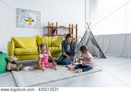 Kindergarten Teacher Sitting On Carpet And Playing With Toddler Girl With Down Syndrome Near Child I