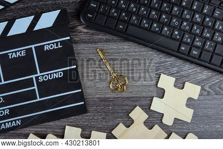 Cinematic  Clapper, Pc Keyboard, Golden Key And Puzzle Pieces On A Table Top View