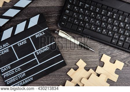 Cinematic  Clapper, Pc Keyboard, Pen And Puzzle Pieces On A Table Top View