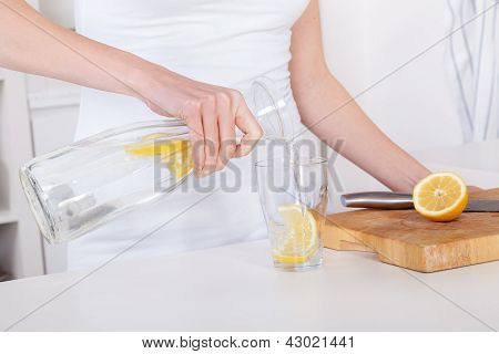Young Woman Preparing And Drinking Lemonade In Her Kitchen