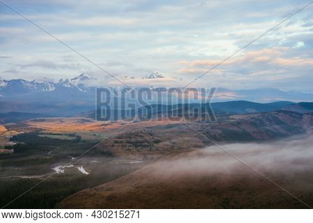 Scenic Alpine Landscape With Low Clouds In Vast Plateau With Mountain River And Forest In Sunlight O