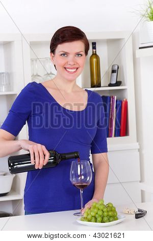 Young Woman Pouring Red Wine In A Glass In Her Kitchen