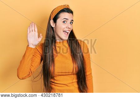 Young brunette teenager wearing casual yellow sweater waiving saying hello happy and smiling, friendly welcome gesture