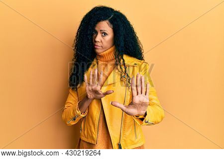 Middle age african american woman wearing wool winter sweater and leather jacket moving away hands palms showing refusal and denial with afraid and disgusting expression. stop and forbidden.