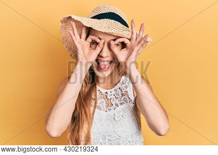 Young caucasian woman wearing summer hat doing ok gesture like binoculars sticking tongue out, eyes looking through fingers. crazy expression.