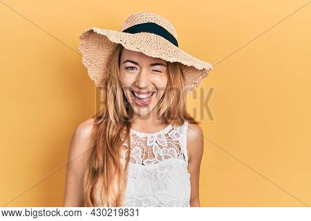 Young caucasian woman wearing summer hat winking looking at the camera with sexy expression, cheerful and happy face.